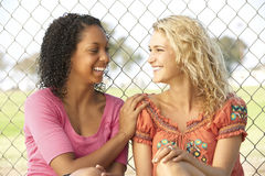 Teenage Girls Sitting Together In Playground Royalty Free Stock Photos