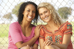 Teenage Girls Sitting Together In Playground Stock Photo