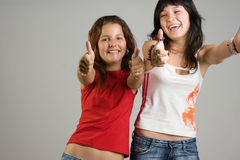 Teenage girls smiling. A studio view of two happy teenage girls reaching out with open arms and smiling happily Royalty Free Stock Image