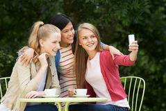 Teenage Girls Taking Photo On Mobile Phone At Outdoor cafe Royalty Free Stock Image