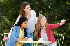 Teenage Girls Taking Photo On Mobile Phone At Outdoor cafe Royalty Free Stock Images