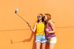 Teenage girls taking picture by selfie stick Royalty Free Stock Photo