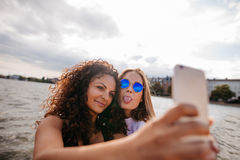 Teenage girls taking selfie with smart phone by the lake Royalty Free Stock Photo