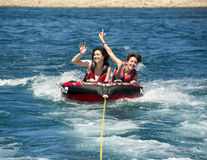 Teenage girls tubing. A nineteen year-old Amerasian girl and her fifteen year-old teenage female cousin are having fun being pulled by a speedboat on an inflated Royalty Free Stock Image