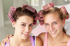 Teenage girls using curlers in their hair Royalty Free Stock Photo