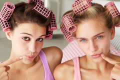 Teenage girls using curlers in their hair Stock Photo
