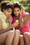 Teenage girls using phone. Outdoors Stock Images