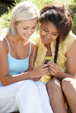 Teenage girls using phone outdoors Royalty Free Stock Image