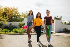 Teenage girls walking holding skateboards royalty free stock images