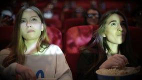 Teenage girls watching movie in cinema. Two Young woman watching movie in cinema and eating popcorn stock footage