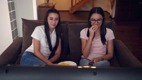 Teenage girls watching tv and eating popcorn at home. Teenage girls watching tv and relaxing with popcorn at home. Handheld movement 4k stock video footage