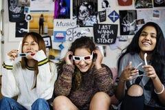 Teenage girls wearing 3d movie eyeglasses enjoying laughing and watching TV stock photo