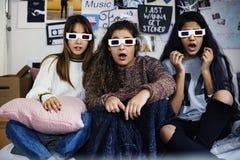 Teenage girls wearing 3d movie eyeglasses. Surprised scared and watching TV stock images