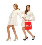 Teenage girls in white coats with shopping bags Royalty Free Stock Photo