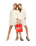 Teenage girls in white coats with shopping bags Stock Images
