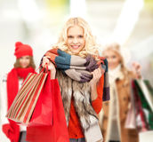 Teenage girls in winter clothes with shopping bags Royalty Free Stock Photos