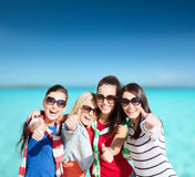Teenage girls or young women showing thumbs up. Summer, holidays, vacation, happy people concept - beautiful teenage girls or young women showing thumbs up royalty free stock photos