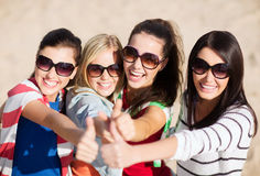 Teenage girls or young women showing thumbs up. Summer, holidays, vacation, happy people concept - beautiful teenage girls or young women showing thumbs up stock photos