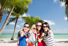 Teenage girls or young women showing thumbs up. Summer, holidays, vacation, happy people concept - beautiful teenage girls or young women showing thumbs up royalty free stock photography