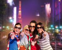 Teenage girls or young women showing thumbs up. Summer, holidays, vacation, happy people concept - beautiful teenage girls or young women showing thumbs up in Royalty Free Stock Photo