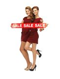 Teenage girsl in red dresses with sale sign Royalty Free Stock Image