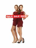 Teenage girsl in red dresses with sale sign Stock Photos