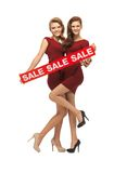 Teenage girsl in red dresses with sale sign Stock Photo