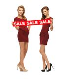 Teenage girsl in red dresses with sale sign Royalty Free Stock Images