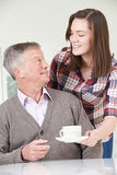 Teenage Granddaughter Bringing Grandfather Hot Drink Royalty Free Stock Photos