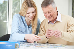 Teenage Granddaughter Helping Grandfather With Jigsaw Puzzle Stock Images