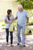 Teenage Granddaughter Helping Grandfather With Shopping Royalty Free Stock Images