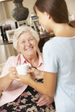 Teenage Granddaughter Making Grandmother Hot Drink At Home Stock Image