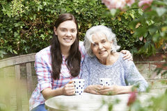 Teenage Granddaughter Relaxing With Grandmother In Garden Royalty Free Stock Image