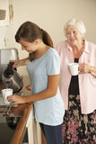 Teenage Granddaughter Sharing Cup Of Tea With Grandmother In Kitchen Royalty Free Stock Images