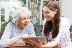 Teenage Granddaughter Showing Grandmother How To Use Digital Tab. Teenage Granddaughter Showing Grandmother How To Use Tablet Computer Stock Photos