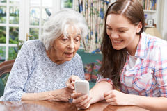 Teenage Granddaughter Showing Grandmother How To Use Mobile Phon Stock Photo
