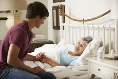 Teenage Grandson Visiting Grandmother In Bed At Home Stock Photo