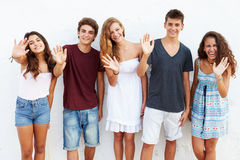 Teenage Group Leaning Against Wall Waving Stock Photo
