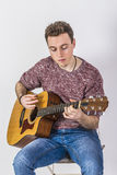Teenage guitar player sits on a chair and plays western guitar Royalty Free Stock Images