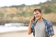Teenage guy talking on phone on the beach. Happy teenage guy talking on mobile phone walking on the beach Royalty Free Stock Images
