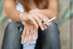 Teenage hands holding cigarette Stock Photos