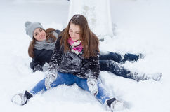 Teenage happy smiling girls playing in deep snow on cold winter stock images
