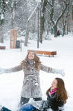 Teenage happy smiling girls playing in deep snow on cold winter Royalty Free Stock Photography