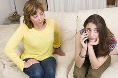 Teenage and her mother have an argument about her phone at home.  Stock Photography