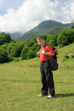 Teenage hiker. Teenage boy carries a rucksack on a walking trip in the mountains Stock Photo