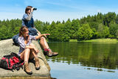 Teenage hikers birdwatching at lake Royalty Free Stock Images
