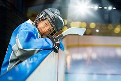 Teenage hockey player leans on the boards of rink. Teenage hockey player in uniform leans on the boards of ice rink and watches the game stock images