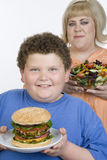 Teenage Holding Plate Of Hamburger. Portrait of teenage boy holding plate of hamburger with mature women holding vegetable salad in the background isolated over royalty free stock images