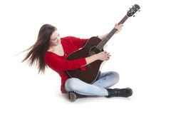 Teenage holds guitar in studio Royalty Free Stock Images