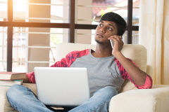 Teenage indian male using. Laptop and having phone conversation Royalty Free Stock Photography